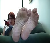 Red hair bitch play with her foot.