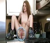 Kleine roodharige tiener met kleine tietjes speelt in de keuken