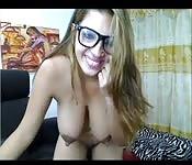 Rondborstige vrouw met een bril geeft show voor de cam