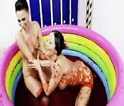 Zwei Mädchen die in einem schmutzigen Pool spielen